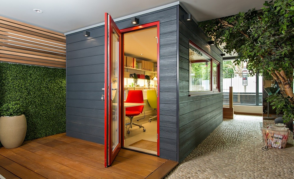 Urbano garden room with grey composite cladding and red framed glazing